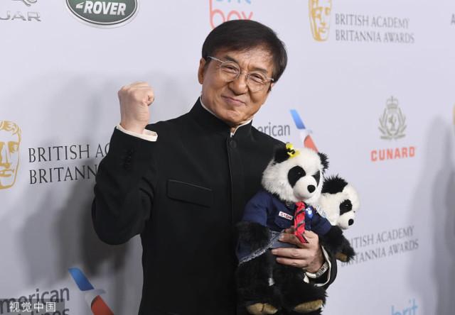 """当地时间2019年10月25日,美国比弗利山庄,2019英国电影电视艺术学院""""大不列颠奖""""红毯,成龙身穿中式服装,手举国宝大熊猫握拳卖萌,十分可爱。据外媒报道,成龙获得""""大不列颠奖""""的""""艾伯特 R 布洛柯里奖"""",此奖项由BAFTA洛杉矶分部颁发,表彰成龙在全球娱乐业做出的突出贡献。"""